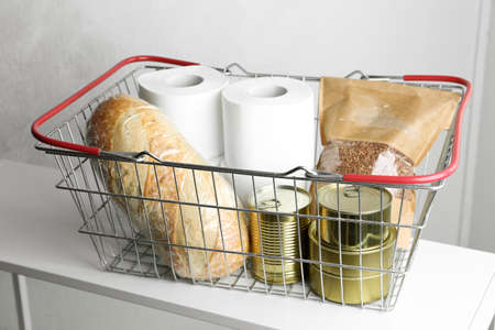 Shopping basket with products and toilet paper rolls on table indoors. Panic caused by virus