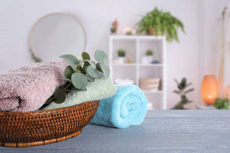 Fresh towels and eucalyptus branches on grey wooden table in bathroom. Space for text