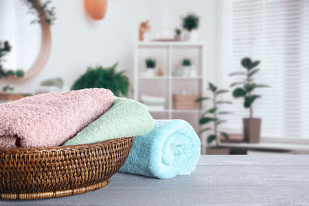 Wicker basket with clean soft towels on grey wooden table in bathroom. Space for text