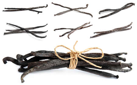 Set with dried vanilla pods on white background