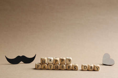 Words HAPPY FATHER'S DAY made with wooden cubes on beige background. Space for text