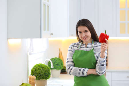 Young woman with apron and bell pepper in kitchen Imagens