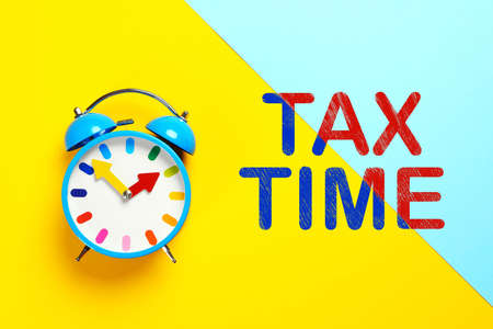 Time to pay taxes. Alarm clock on color background, top view
