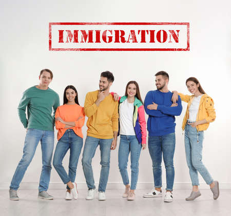 Immigration concept. Group of young people standing near light wall Imagens