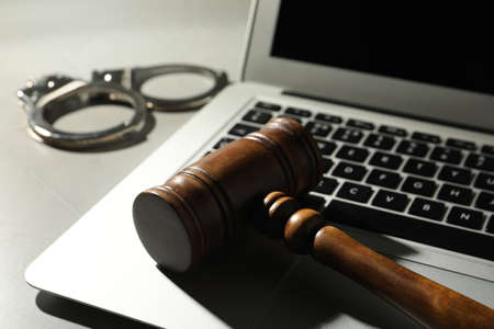 Laptop, wooden gavel and handcuffs on grey table, closeup. Cyber crime