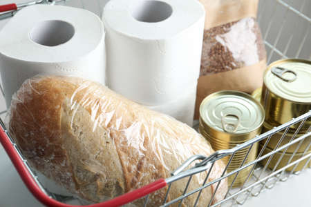 Shopping basket with products and toilet paper rolls on table, closeup. Panic caused by virus