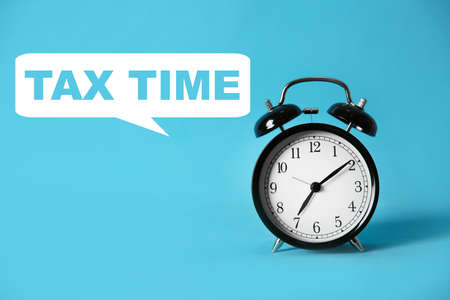 Time to pay taxes. Alarm clock on light blue background