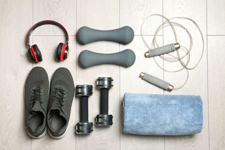 Set of fitness equipment and accessories on wooden background, flat lay Фото со стока