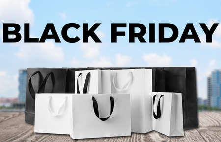 Black Friday. Many shopping bags on wooden surface