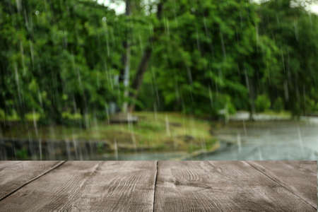 Empty wooden table outdoors on rainy day