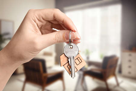 Woman with key in new modern apartment, closeup