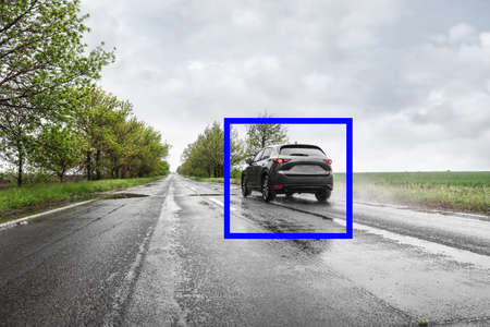 Wet suburban road with scanner frame on car outdoors. Machine learning Standard-Bild