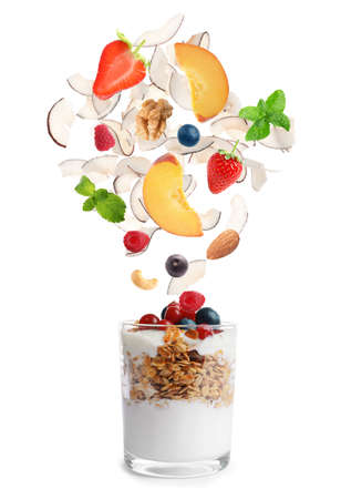 Delicious yogurt with granola, nuts, fruits and berries on white background