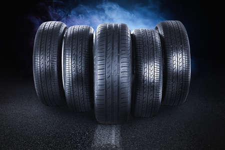 Car tires and smoke on road against black background