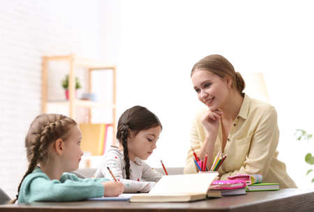 Mother helping her daughters with homework at table indoors