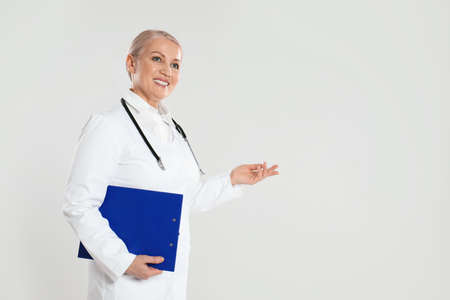 Mature doctor with clipboard on light grey background. Space for text 스톡 콘텐츠