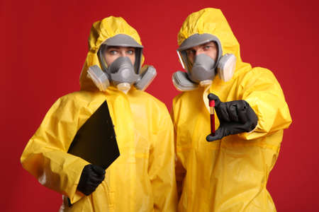 People in chemical protective suits with blood sample and clipboard on red background. Virus research