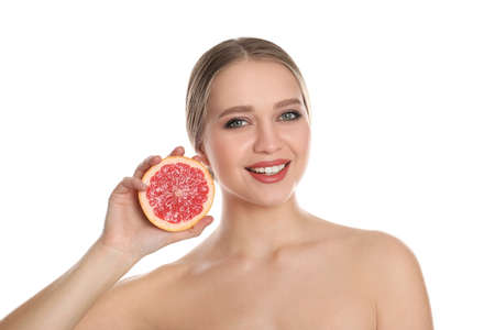 Young woman with cut grapefruit on white background. Vitamin rich food
