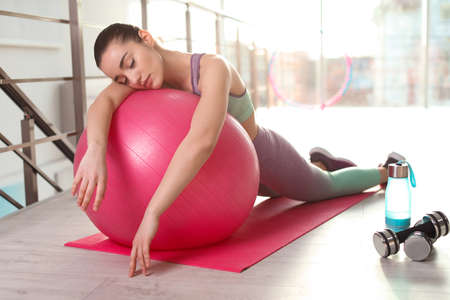Lazy young woman with sport equipment sleeping on yoga mat indoors