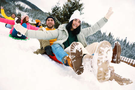 Group of friends having fun and sledding on snowy day. Winter vacation