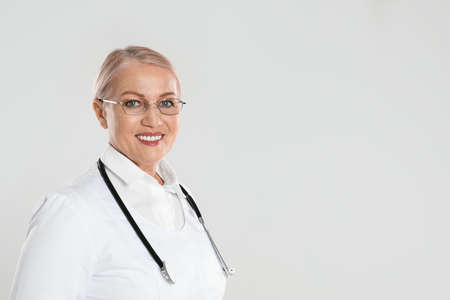 Portrait of mature doctor with stethoscope on light grey background. Space for text