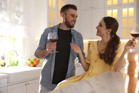 Lovely young couple drinking wine while cooking together in kitchen