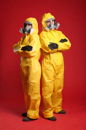 Man and woman wearing chemical protective suits on red background. Virus research