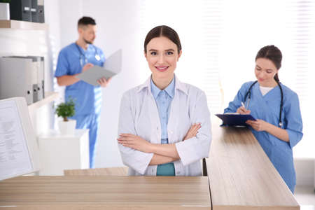 Portrait of female doctor at counter in modern clinic 스톡 콘텐츠