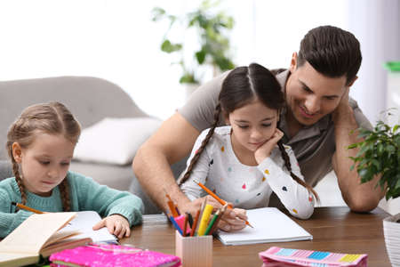 Father helping his daughters with homework at table indoors Banque d'images
