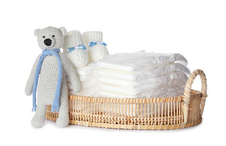 Wicker tray with disposable diapers, toy bear and child's booties on white background