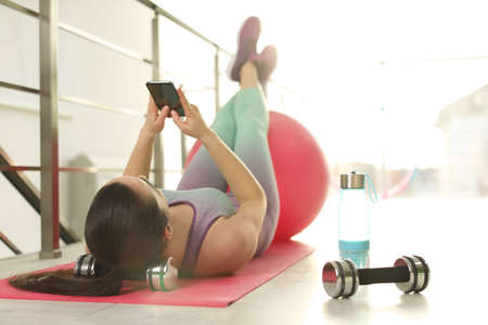 Lazy young woman with smartphone on yoga mat indoors