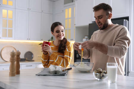 Lovely young couple cooking dough together in kitchen