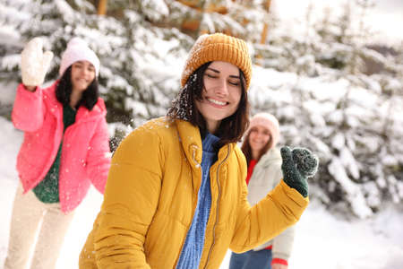 Happy friends playing snowballs outdoors. Winter vacation