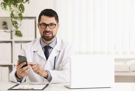 Male doctor with smartphone at table in office