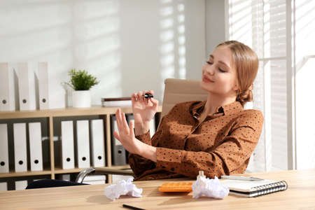 Lazy office worker doing manicure at desk indoors