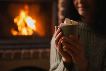 Woman with cup of sweet cocoa near fireplace indoors, closeup
