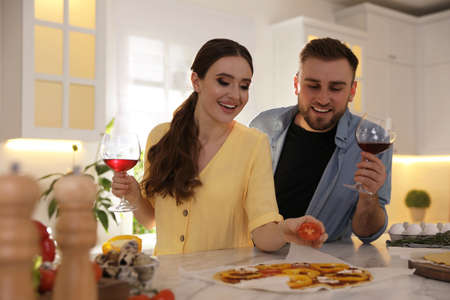 Lovely young couple cooking pizza together in kitchen Banque d'images