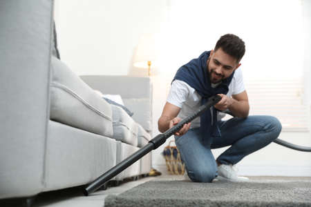 Young man using vacuum cleaner at home