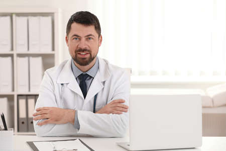 Portrait of male doctor in white coat at workplace