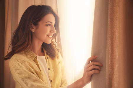 Happy woman opening window curtains at home Banque d'images