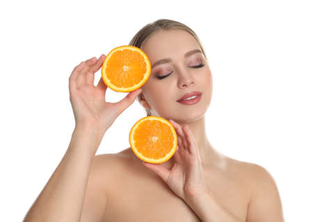 Young woman with cut orange on white background. Vitamin rich food