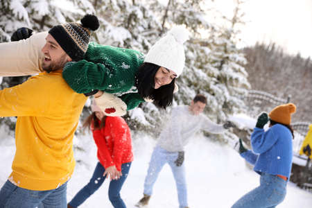 Group of friends playing snowballs outdoors. Winter vacation