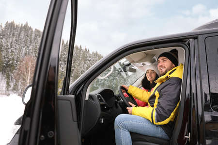 Happy couple in car outdoors. Winter vacation Banque d'images