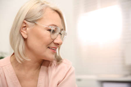 Beautiful mature woman in glasses at home. Space for text