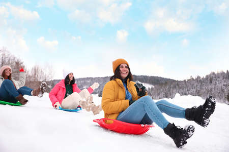 Group of friends having fun and sledding on snow. Winter vacation 版權商用圖片