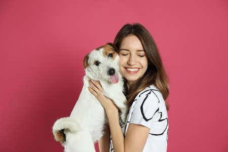 Young woman with her cute Jack Russell Terrier on pink background. Lovely pet