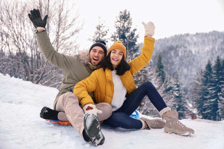 Happy couple sliding on snowy hill. Winter vacation