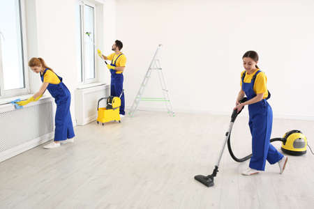 Team of professional janitors in uniforms cleaning room