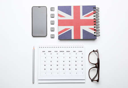 Calendar, notebook, glasses and mobile phone on white background, top view. Learning English Stok Fotoğraf