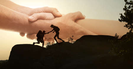 Double exposure of people climbing up mountain and helping hand Stock Photo